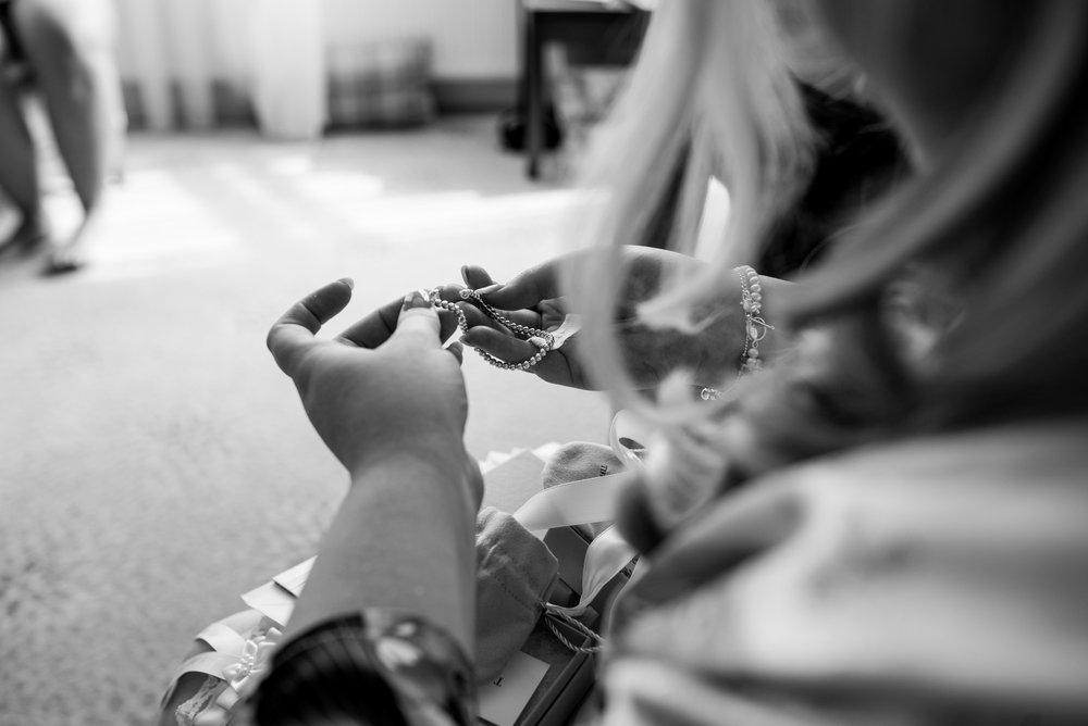 The bride looks at her new bracelet off her groom