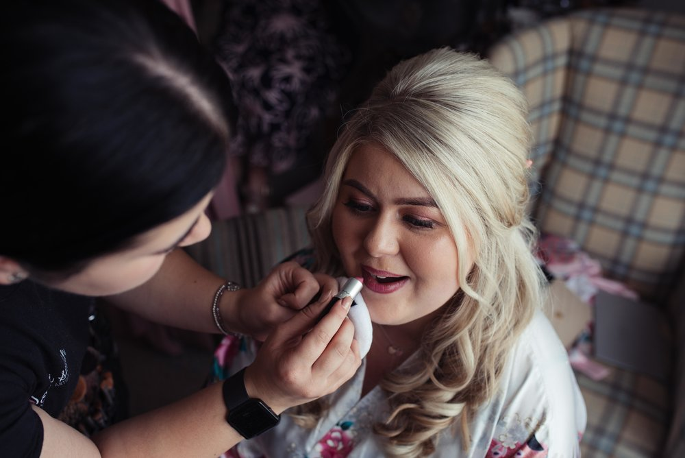 The bride has the final touches of her makeup done in front of the window