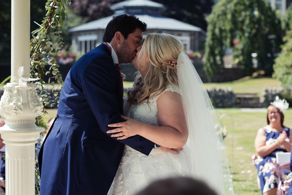 The bride and groom share their first kiss at the inn on the lake