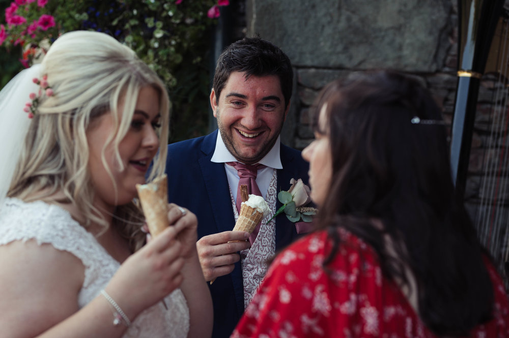 The bride and groom eat ice cream and chat to another wedding guest
