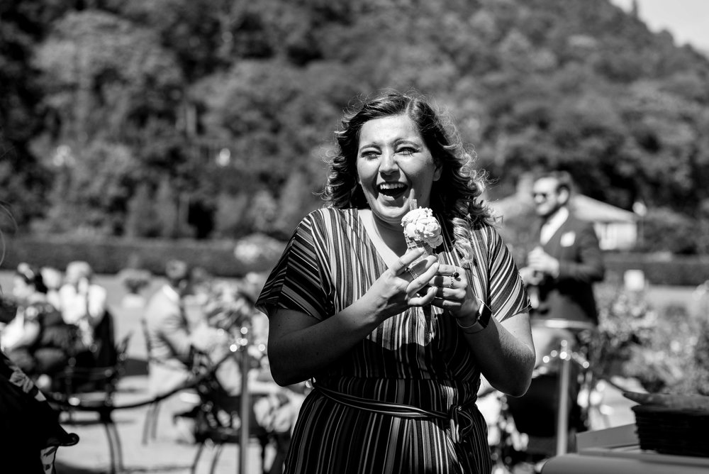 One of the wedding guests laughs out loud as she eats her ice cream