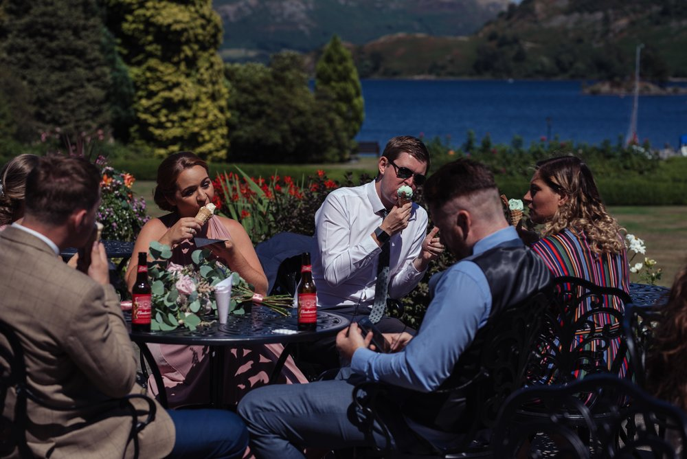A group of wedding guests sit and eat their ice cream outside the inn on the lake