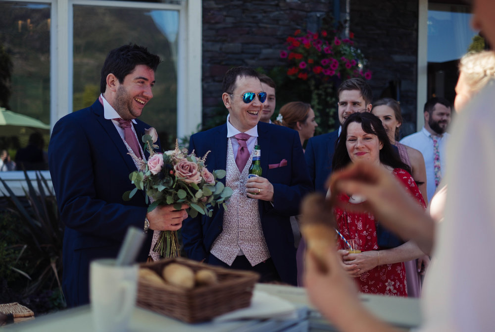 The groom holds the bridesmaids flowers as she gets an ice cream at the inn on the lake