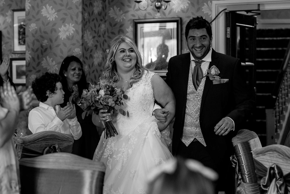 The bride and groom make their way into the wedding breakfast room at the inn on the lake