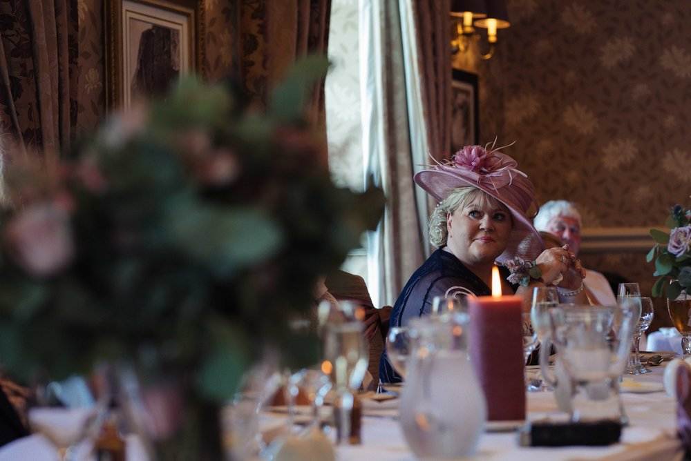 The mother of the groom watches her husband deliver his speech