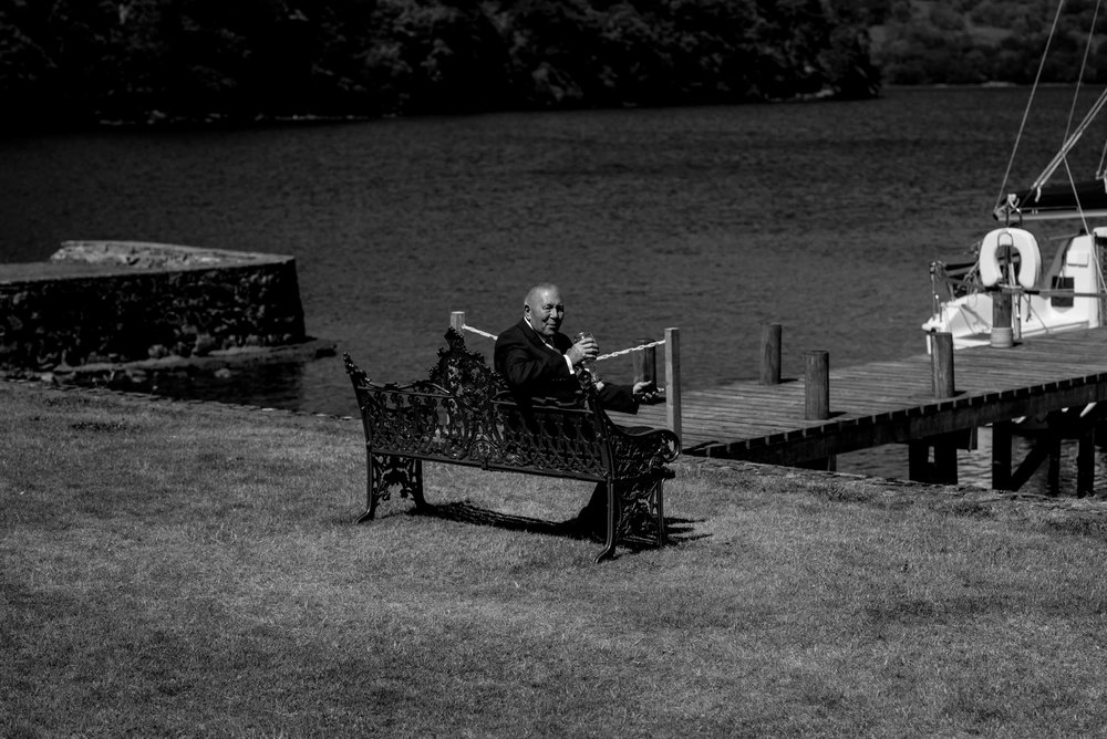 Grandad sits on his own on a bench right by the edge of the lake
