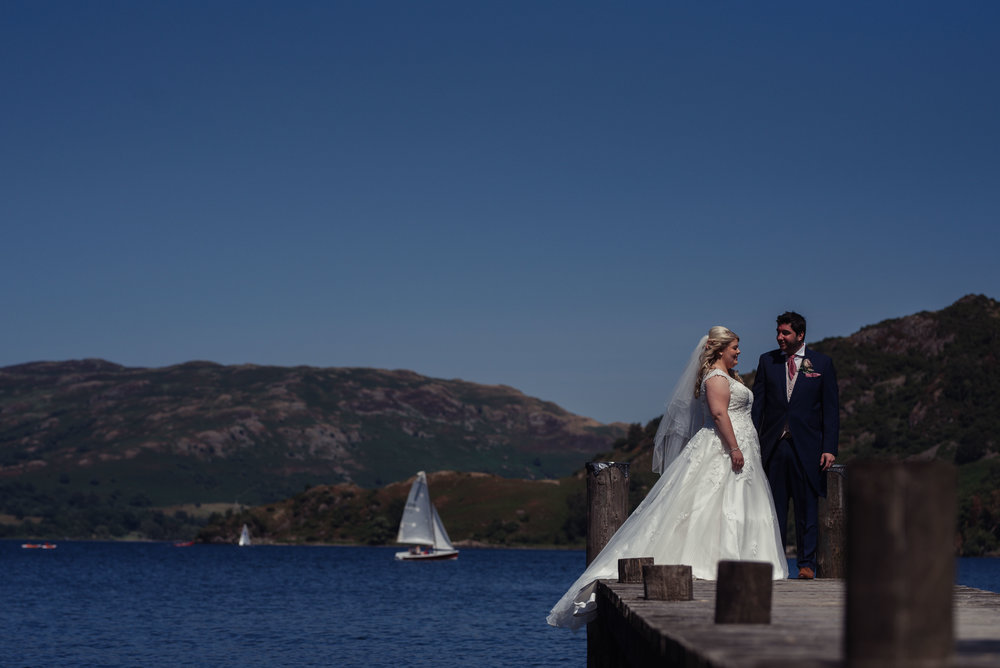 The bride and groom pose on the jetty of the inn on the lake for their wedding photography