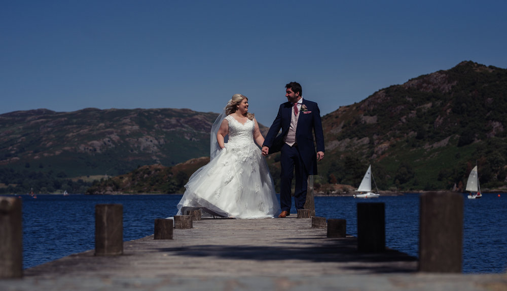 The bride and groom walk down the pier towards the gardens during their wedding photography portraits