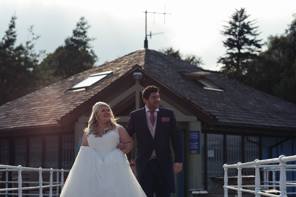 The bride and groom walk towards the ullswater steamer, lit with milky sunshine