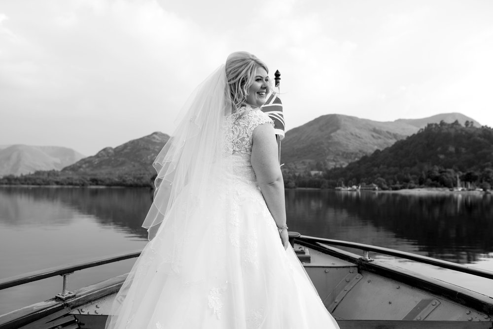 The bride stands at the front of the boat and turns to face her guests