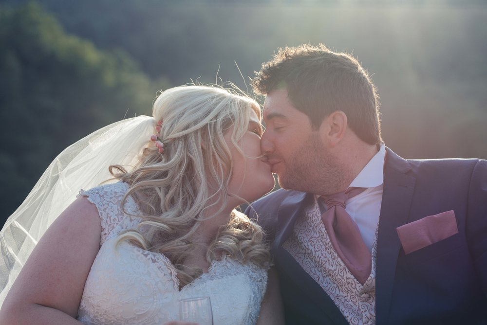 The bride and groom share a kiss together sitting on the boat