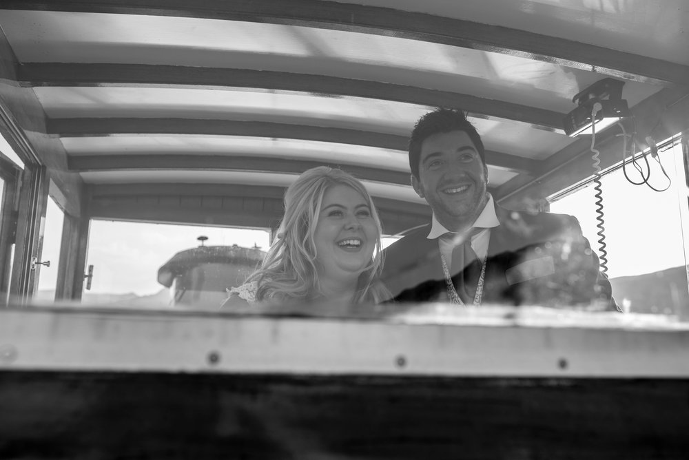 The bride and groom drive the ullswater steamer with smiles on their faces