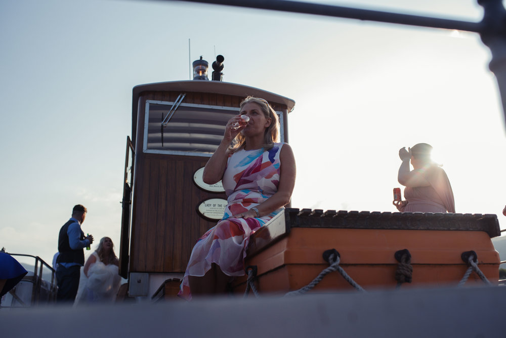 A wedding guest sits on the boat and drinks her prosecco