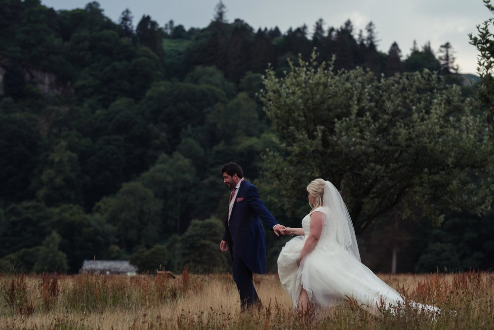 The groom holds the brides hand as they walk through a field on the shore of Ullswater