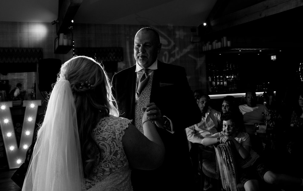The brides father looks lovingly at his daughter during their first dance