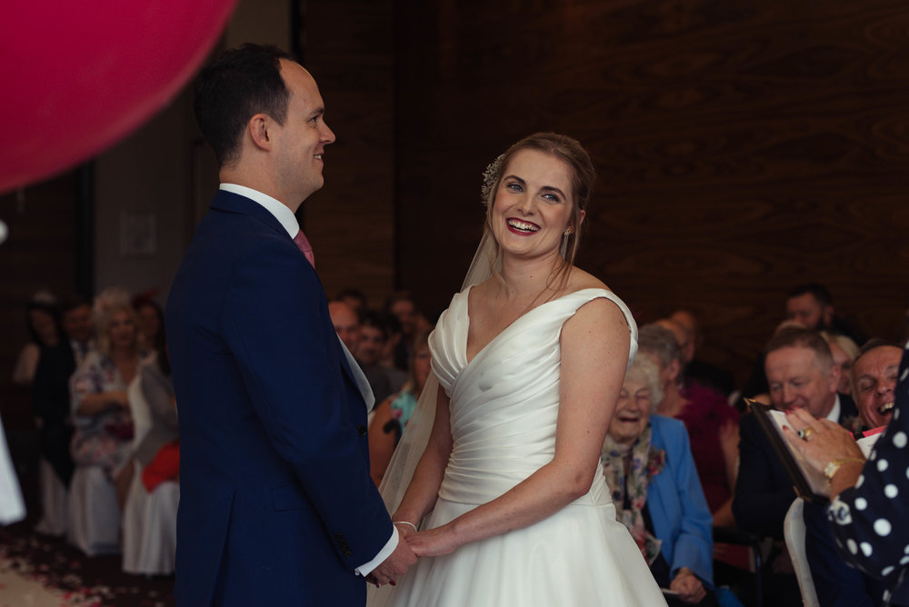 The bride and groom have a giggle together during the wedding ceremony