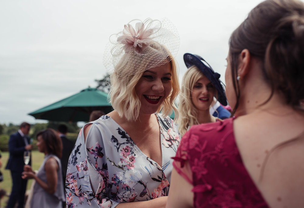 A wedding guest with a floral dress chats to one of the bridesmaids