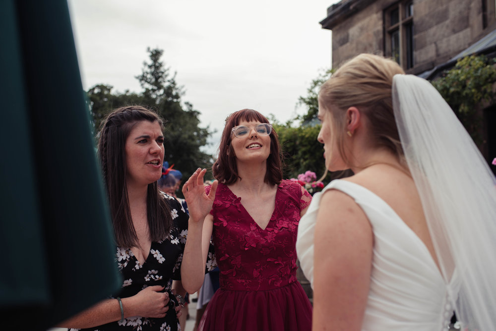 A bridesmaid has a laugh with the bride outside rookery hall
