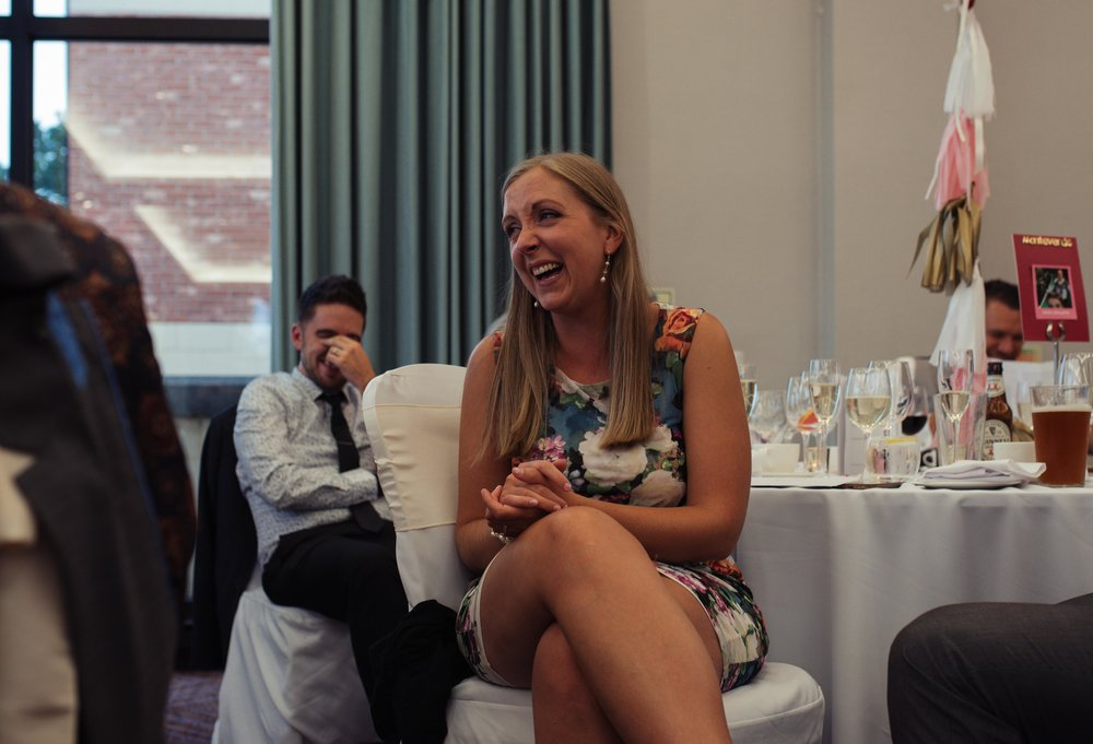 Wedding guest sits cross legged laughing during the speeches