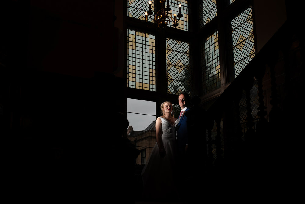 Bride and groom lit up with a flash inside rookery hall