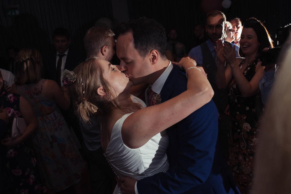 The bride and groom share a kiss on the dance floor