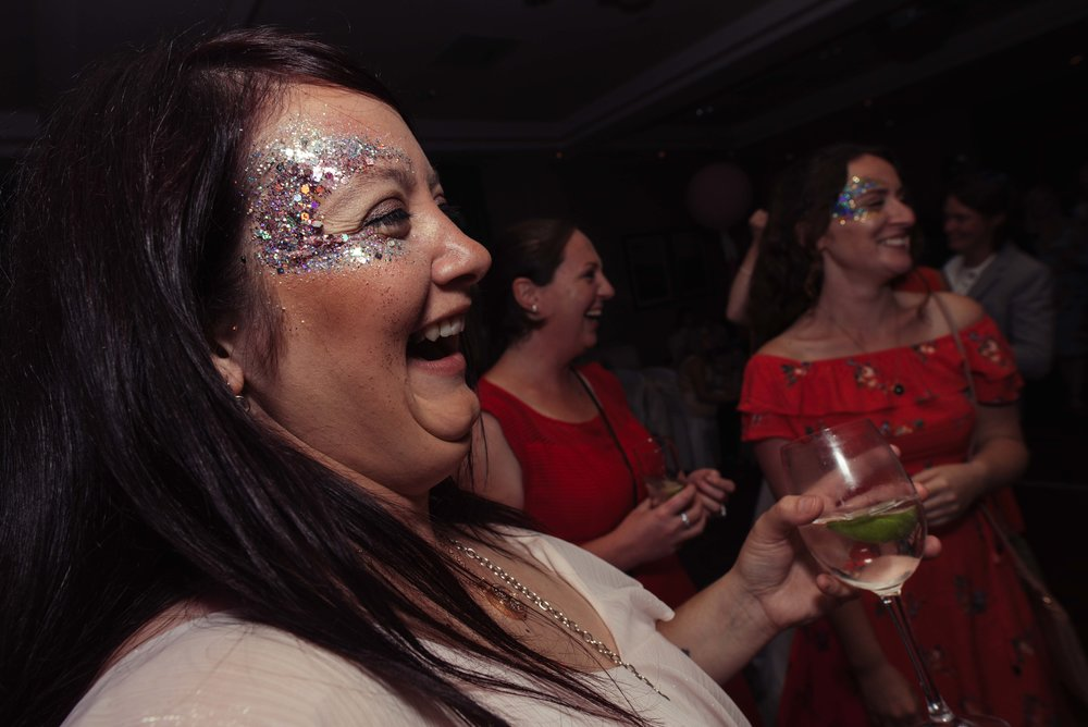 A very sparkly-faced wedding guest on the dance floor