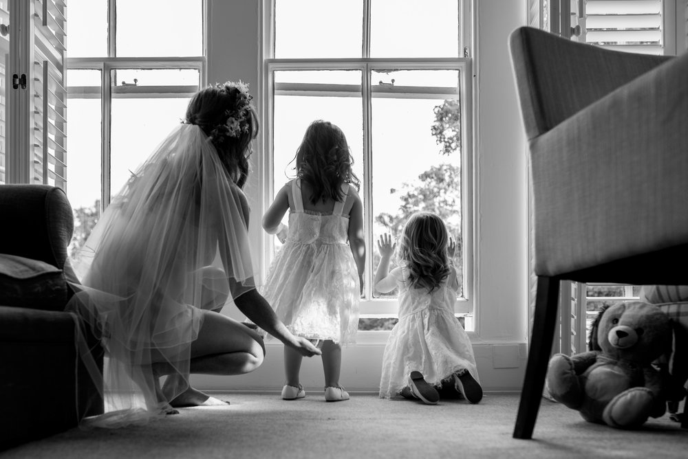 The bride stands in the bedroom window with her flower girls