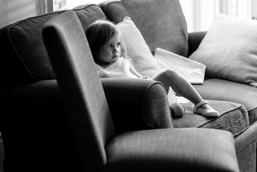 A flower girl sits on the sofa and snoozes