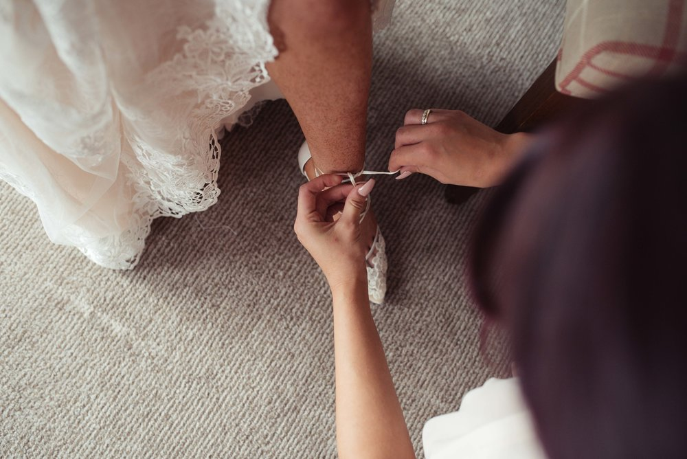 The brides sister helps her put on her lace wedding shoes