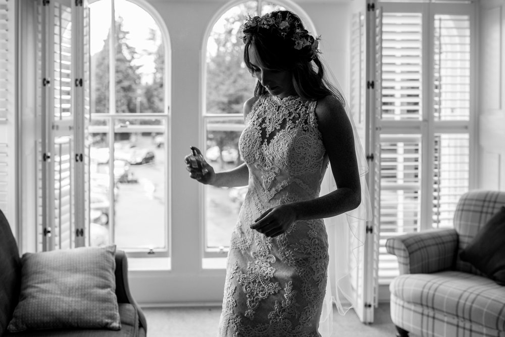 The bride applies perfume before heading down for her Cumbrian wedding