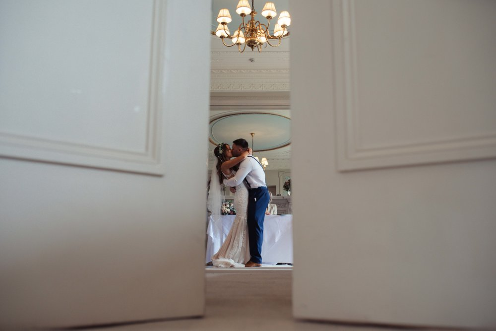 The bride and groom share a kiss through a door way