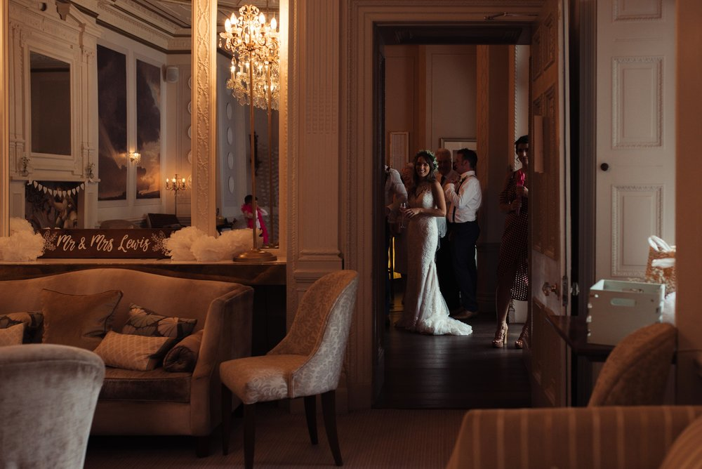 The bride stands in the doorway chatting to her guests