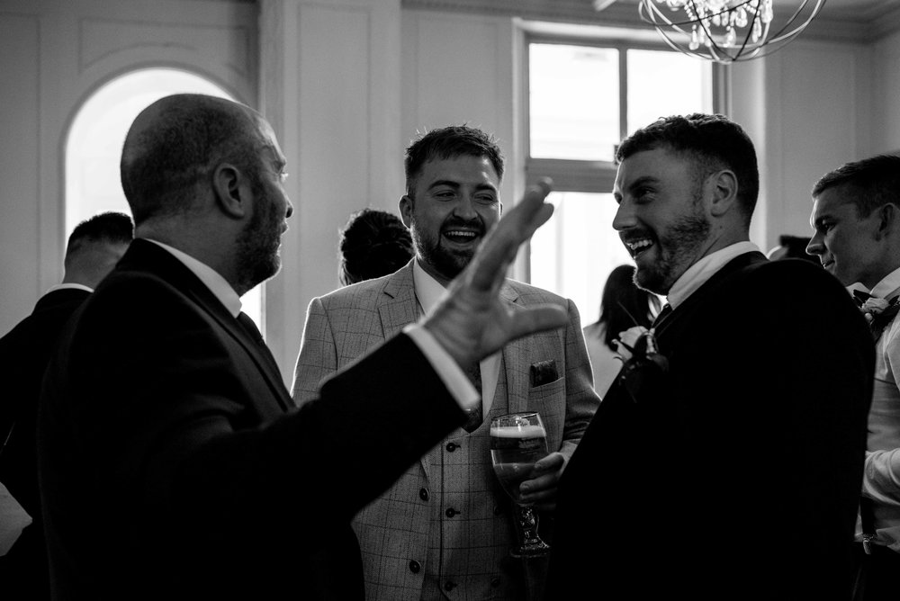 A male wedding guest laughs out loud in the Belsfield