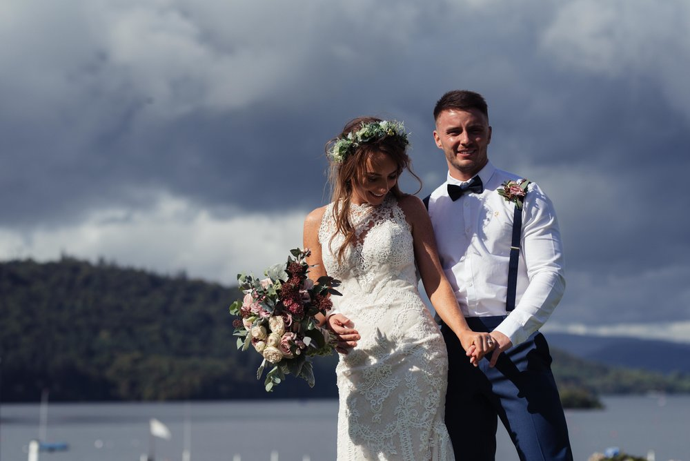 Bride and groom stand against a stormy sky