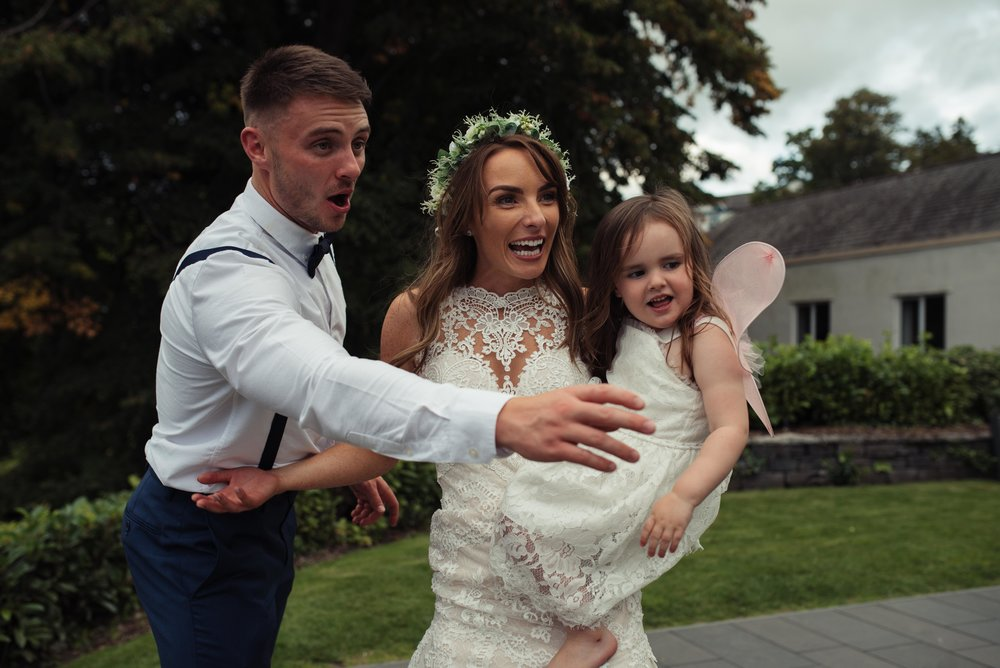 The bride and groom chase bubbles with their daughter