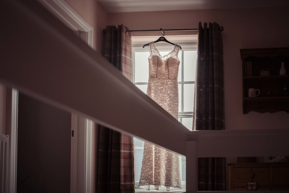 The brides dress hanging in the hallway in front of the window