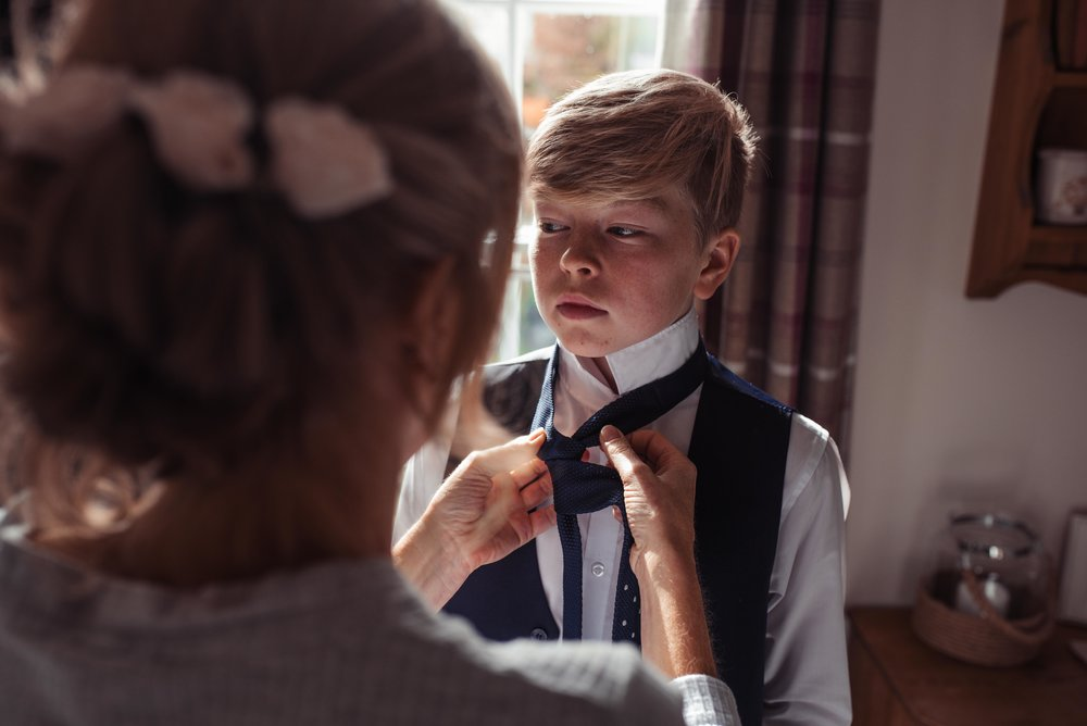 The bride helping put on her sons tie