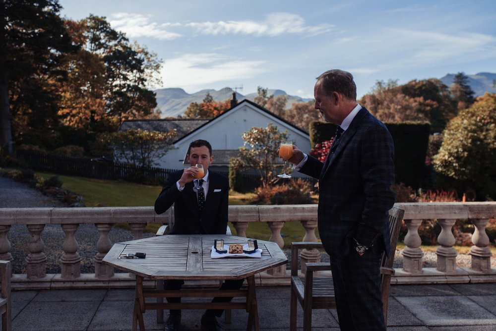 The groom and his best man enjoy orange juice and cake on the terrace before the wedding