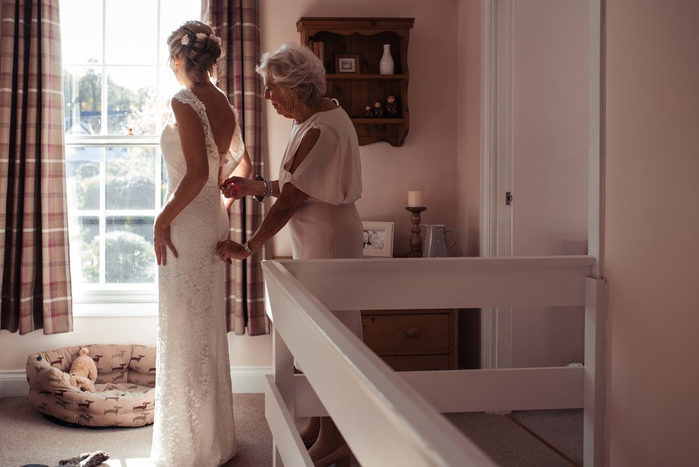 The brides mother helps the bride put her dress on in front of the window