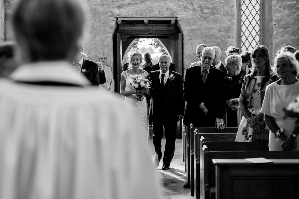 The bride enters the church with her father on her arm