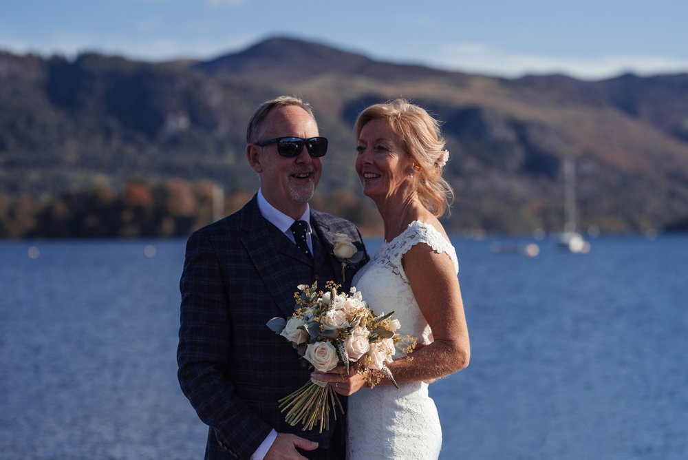 The bride and groom stand on the banks of the lake with sunglasses on