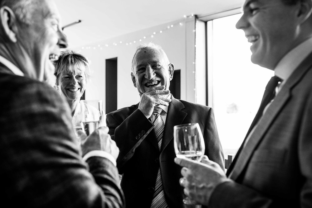 A man has a big laugh during the wedding welcome drinks