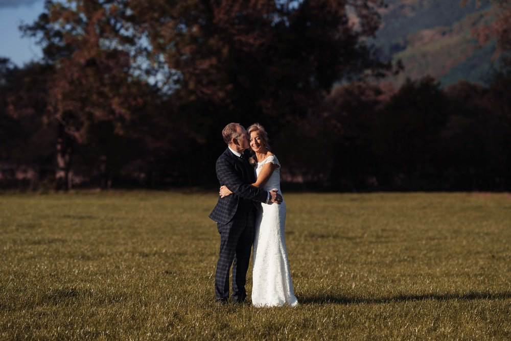 The bride and groom stand in an open field