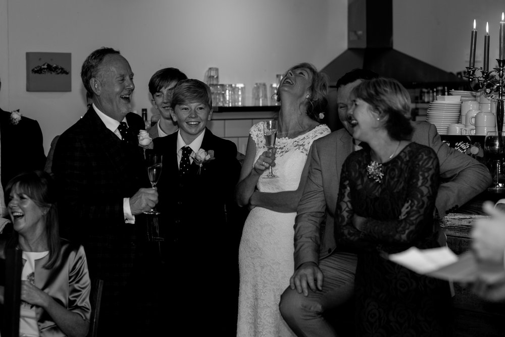 The bride and groom and their family laugh during one of the speeches
