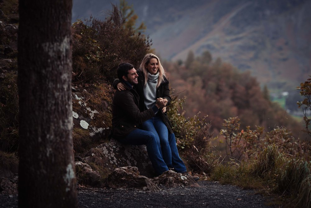 The bride and groom sit on rocks at surprise view in the lake district