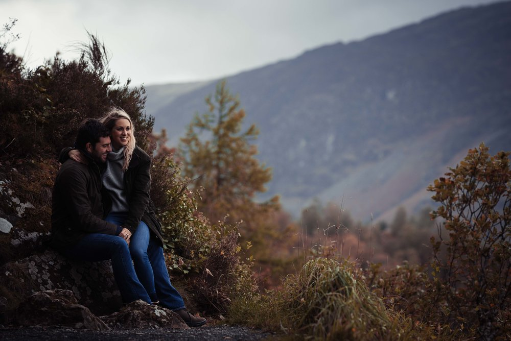 The bride and groom sit against a rock and loo out over the view of the lake district