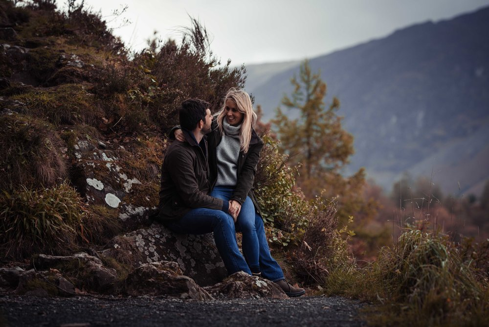 The bride and groom have a giggle together sitting on the rocks in Keswick at Surprise View