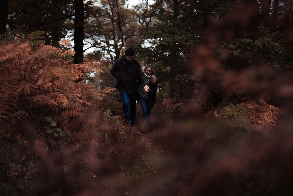 The bride and groom walking through the woods at surprise view