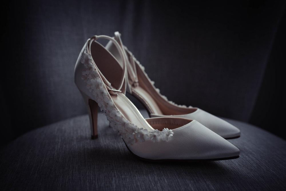 Brides wedding shoes sitting on a grey chair