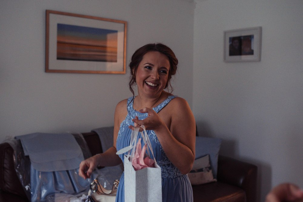 A bridesmaid in blue receives her gift off the bride